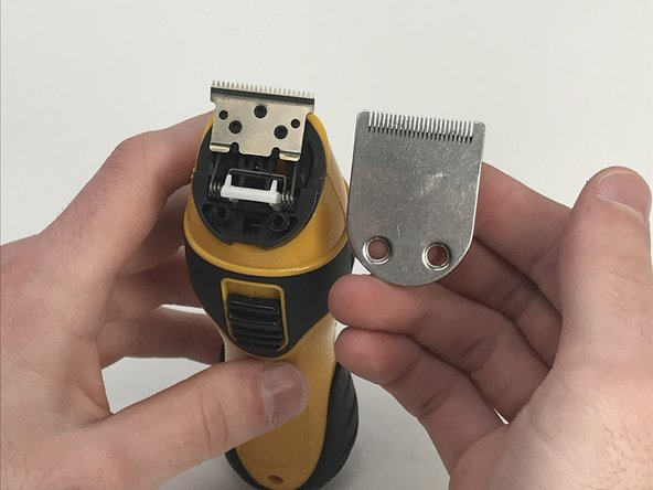 Lift both of the trimmer blades off of the plastic guard.