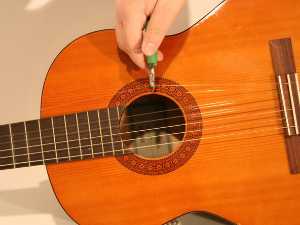 Cutting a string under tension could cause injury. Ensure that all strings are loose before attempting the next  step.
