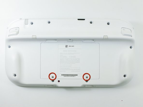 Face the GamePad down and unscrew the two Phillips #00 screws which are attached to the battery cover.