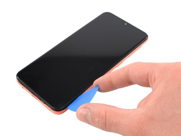 Slide the opening pick along the right edge to the top right corner to unclip the plastic clips.