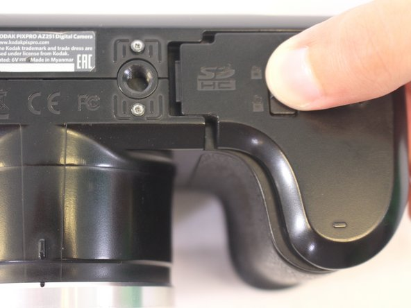 Press down on the battery cover and slide outwards to open.