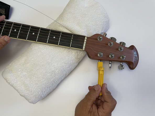 Place the guitar neck on an elevated surface (ex. bundle towels, pillow, etc.). Remove the string with a string winder until it is loose enough to pull out by hand.