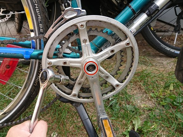 Remove the crank bolts on either side of the crankset by using the 14 mm drive socket to spin the bolts counterclockwise.