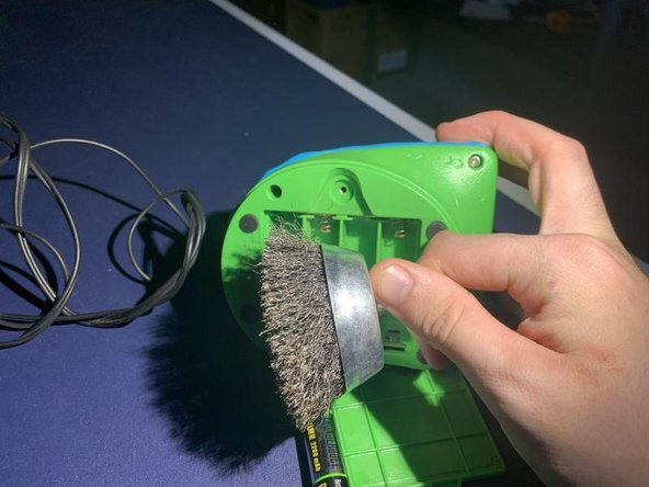 Scrub the metal battery connectors by twirling the steel brush to get a less dull color on the metal and have some luster to it.