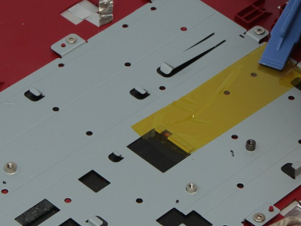Peel the yellow tape off of the back plate to free the keyboard so it can be separated from the plate.