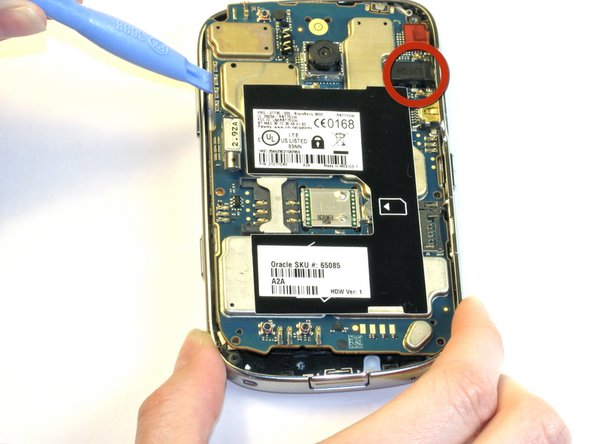 With the same plastic opening tool, lift the motherboard up and out.