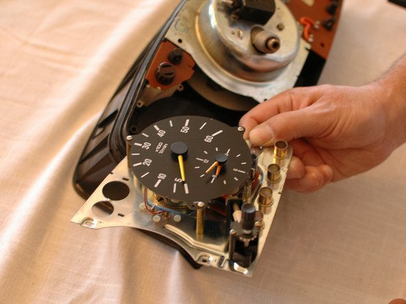 You will now be able to carefully lift the tachometer/clock assembly out of the cluster. Set it aside someplace safe. Do not set it face down, on the needles.