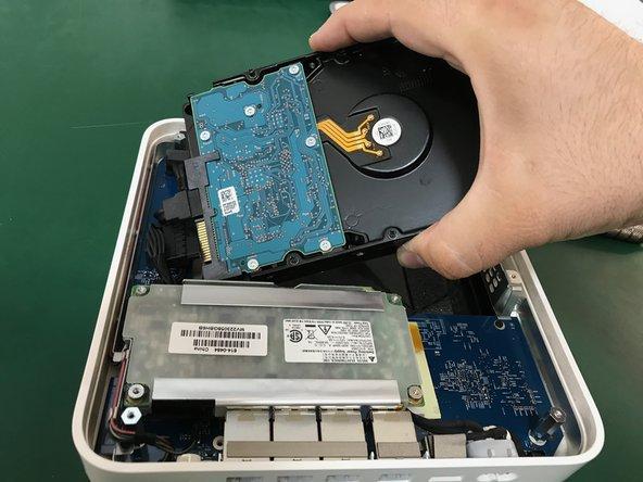 Levantamos un poco el disco duro sin tirar demasiado para no provocar daño en los conectores de corriente y de datos del disco duro.                                                 Retiramos el conector de alimentación del disco duro