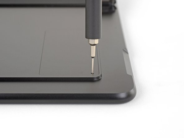 Setze ein SIM-Kartenauswurfswerkzeug oder eine aufgebogene Büroklammer in die kleine Öffnung in der unteren rechten Ecke der Abdeckung über der SIM-Karte und der SSD. Diese findest du nahe der unteren rechten Ecke des Surface.