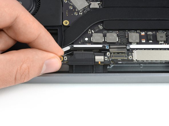 Grab the left side of the display cable assembly and pull it towards the bottom end of the MacBook and away from the  cover spring.