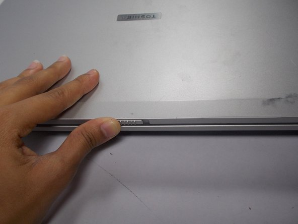 Unlock the laptop by sliding the front tab to the right.