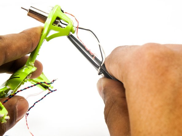 Use the tweezers to push the motors out of their housings.