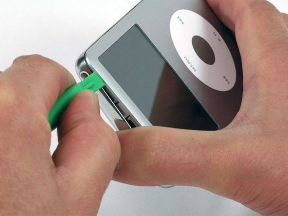 Near the other top corner, insert an opening tool into the seam between the front and back of the iPod