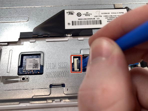 Pop open the ribbon cable piece on the touch pad with the blue plastic spudger.