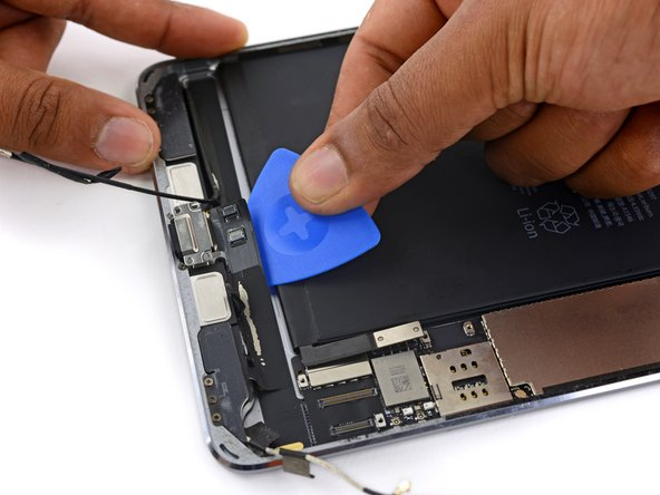 Use an opening pick to separate the adhesive connecting the lightning connector cable to the iPad case.
