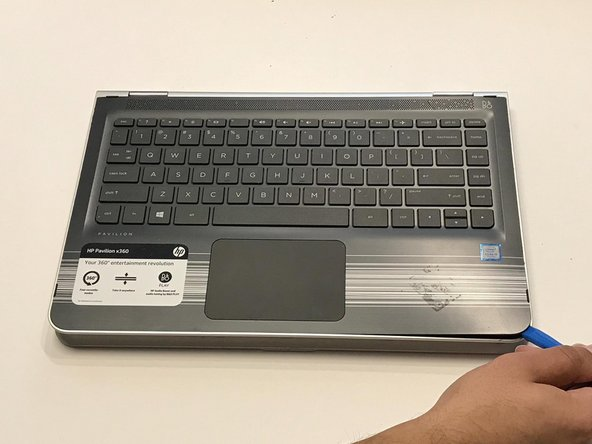 Lift open the laptop screen and flip it around so that the keyboard is facing up.