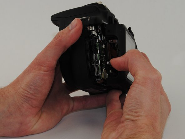 Now that all of the exterior screws have been removed, grip the camera firmly on both sides.