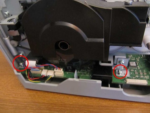 Remove 2 screws on the left hand side, securing the print mechanism to the base through the main circuit board.