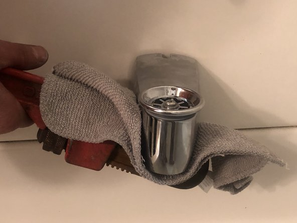 Once too tight to continue twisting, place a rag around the spout and continue to twist with the pipe wrench clockwise (to the right) until fitted against the wall.