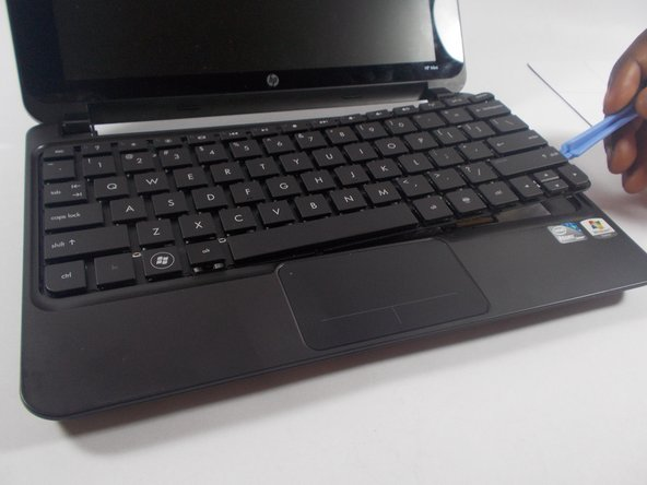 After removing the plastic casing surrounding the keys, carefully lift the full keyboard from the netbook using a plastic opening tool.