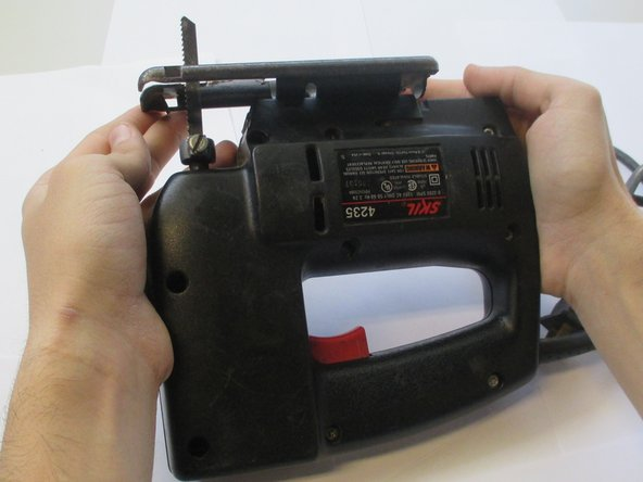 Orient your saw so that the blade is pointing in the opposite direction of your body. Ensure that the screws circled are visible and pointing skyward. This will be the standard position of the Jigsaw for the duration of this guide.