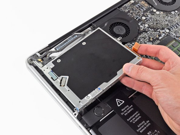 Remove the optical drive from the upper case, minding any cables that may get caught.