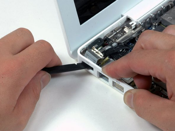 Use a spudger to rotate the MagSafe board up and out of its housing. It may be helpful to pull the lower case out slightly to provide additional clearance.