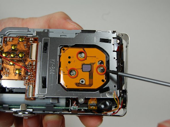 On the back of the camera where the LCD screen was, remove 3 screws located behind the lens.