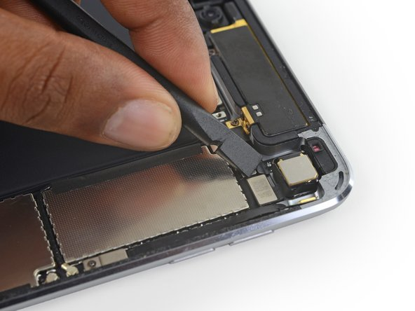 Use the flat end of a spudger to lift the rear-facing camera cable connector from its socket on the logic board.