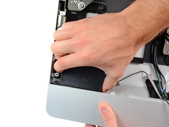 Pull the left speaker toward the center of the iMac to dislodge it from the corner of the outer case.