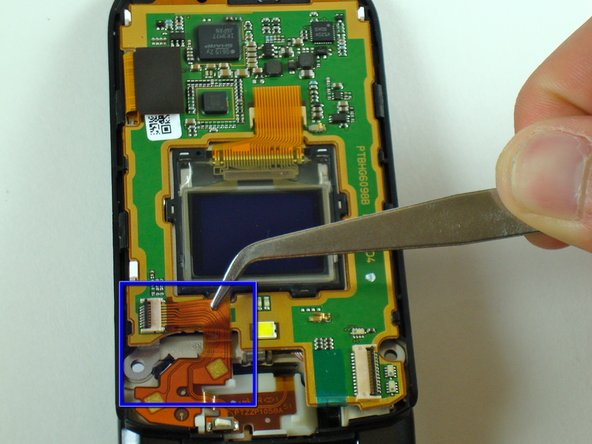 Remove the flexible circuit shown using tweezers (or use your fingers if you can manage a firm grip).