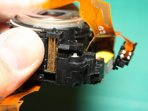 By gently pulling apart the front and back halves of the lens module assembly, we expose a black gear and white gear connecting the larger brass gear to the motor