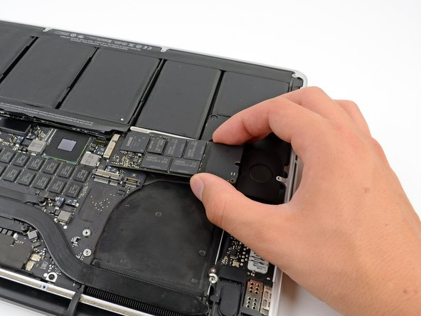 Slightly lift the rightmost side of the SSD and firmly slide it straight away out of its socket on the logic board.