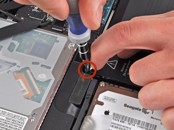 Use the tip of your finger to carefully peel back the corner of the warning label to reveal a hidden Tri-point screw.