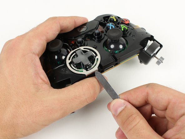 Pry off the metal frame around the D-Pad.