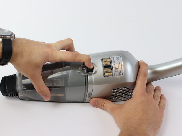 Push down the black button to release the dust cup.