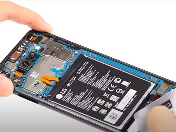 Insert a plastic card at the bottom edge of the battery
