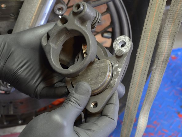 Remove the floating caliper and remaining brake pad from the caliper assembly.