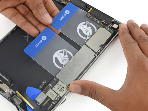 Lift up on the edges of both plastic cards to pry the logic board from the rear case.