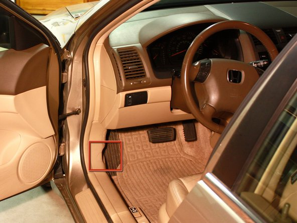 Locate the hood latch beside the driver's side door, right next to the left foot rest.