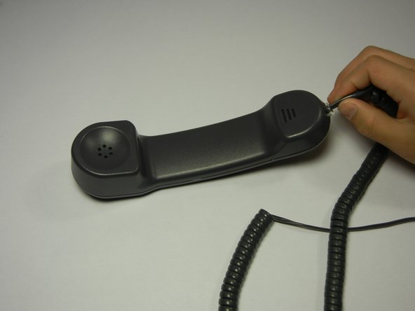 Connect the new handset by squeezing the clip attached to the phone cord and sliding the cord into the bottom slot of the phone.