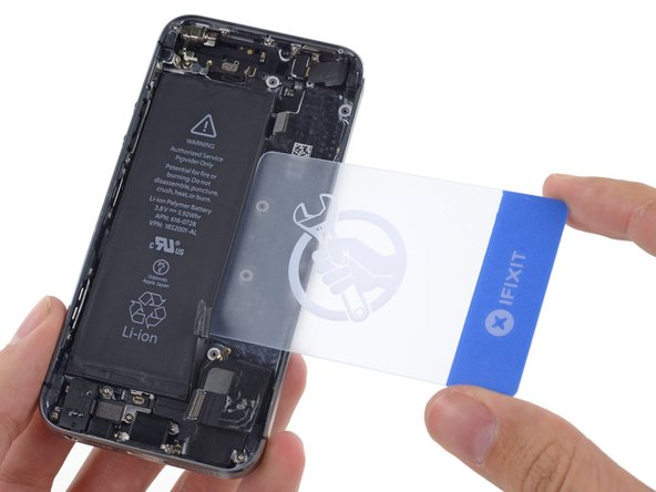 Flip the iPhone back over and insert a plastic card between the case side of the battery and the rear case.