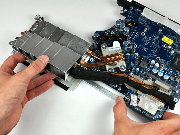 Gently lift the video card assembly from its top edge and rotate it slightly toward the center of the logic board.