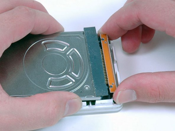 Carefully disconnect the orange ribbon cable from the hard drive.