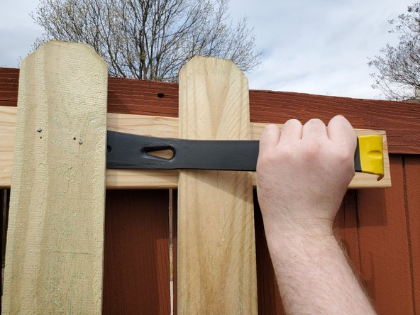 Place the tip of the pry bar under the picket, in line with the nails.