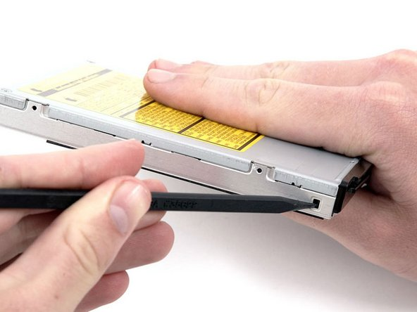 Use a spudger to depress and release the black tab on the left side of the optical drive.