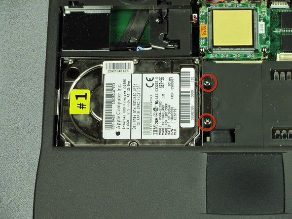 Locate and identify the two screws that attach the hard drive to the computer.