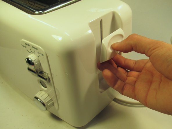 Pull the press handle down and away from the toaster to disconnect the body.