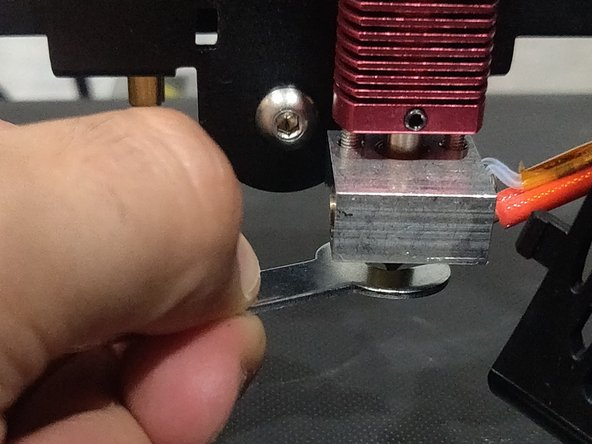 Screw on new nozzle with your fingers.