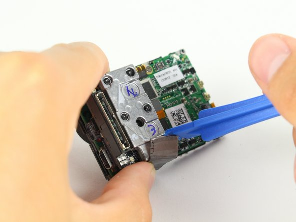 Use the spudger to remove the heat shield tape and detach the image sensor from the motherboard.